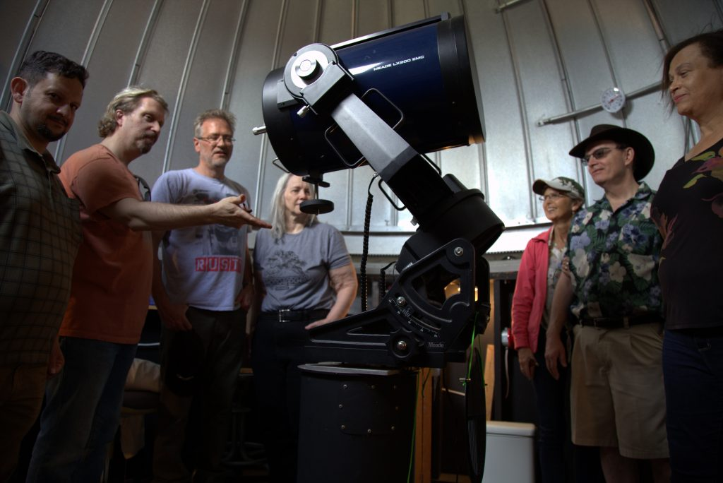 member instructing a group on using the telescope