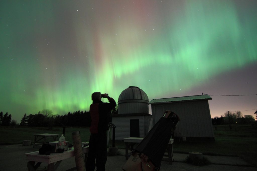 Observer and dome with aurora in the background